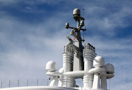 Radar system on to of a ship with blue cloudy sky in the background.